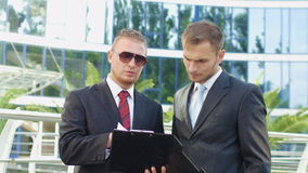Two business men standing next to an office. Building to discuss the case using documents stock video