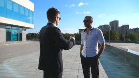 Two business men standing outdoor near office and talking. Businessmen meet and speaking outside in the city street with. Urban background. Communication of stock footage