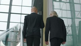 Two business men talking while ascending stairs. Rear view of two corporate executives chatting while ascending stairs in company stock footage