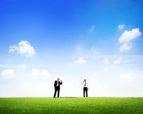 Two Business Men Talking Through Tin Can Phone. Two business men standing in outdoors talking through tin can phone Stock Photo