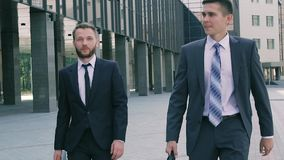 Two business men wearing smart clothes and holding leather cases walking along business center stock video