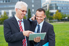Two business men working outdoors Stock Image