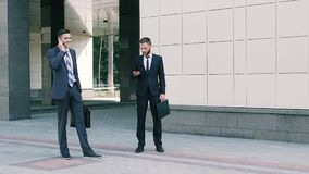 Two business men working outdoors at the middle of working day. One of them is talking on the phone. Slow motion stock video