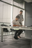 Two business men working together in office. Reading document Royalty Free Stock Image