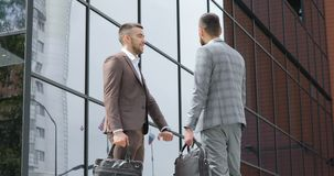 Business partners handshaking. Two young businessmen who are old acquaintances, meet and shake hands. Two business partner shake hands when meeting. business stock footage