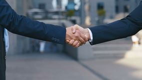 Two business partner shake hands when meeting. Close-up of a handshake of two successful businessmen making a deal. Slow