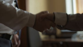 Two business partner shake hands when meeting. Two male business partners shaking hands stock video