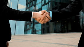 Two business partner shake hands. Slow motion: two businessman partner in suit shake hands. Glass business centre building at background. Close-up steadycam shot stock video footage