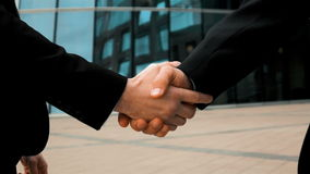 Two business partner shake hands. Slow motion: two businessman partner in suit shake hands. Glass business centre building at background. Teal and orange style stock footage