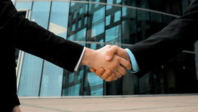 Two business partner shake hands. Slow motion: two businessman partner in suit shake hands. Glossy business centre building at background. Close-up steadicam stock video footage