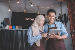 Muslim entrepreneur concept together. Two business partner using tablet in front of their coffee shop. muslim entrepreneur concept Stock Photo