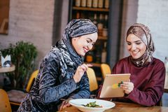 Two Muslim women in cafe, shop online using electronic tablet. Two business partner using tablet in front of their coffee shop Royalty Free Stock Image