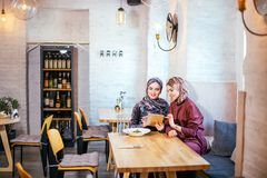 Two Muslim women in cafe, shop online using electronic tablet. Two business partner using tablet in front of their coffee shop Stock Image