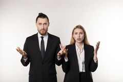 Two business partners in black suits, handsome bearded man and beautiful blonde woman shocked don`t know what to do stock image