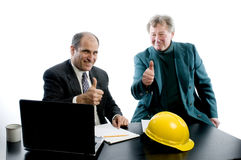 Two business partners at desk shaking hands. Business management senior executives client shaking hands in office retired older men architect builder Royalty Free Stock Images