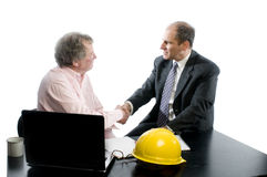 Two business partners at desk shaking hands. Business management senior executives client shaking hands in office retired older men architect builder Stock Image