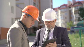 Two business partners in helmets meeting near builds and discussing. 4K stock video footage