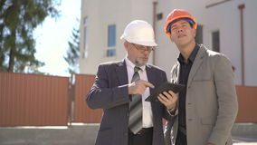 Two business partners looking on building plans on tablet. 4K.  stock footage