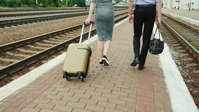 Two business partners with luggage are walking along the railway platform. In the frame you can see only the legs, the. Rear view. Arrival on business trip. POV stock video footage