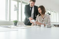 Two business partners a man and a woman calculating expenses and Stock Images