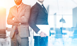 Two business partners in office with skyscrapers, toned Royalty Free Stock Photos