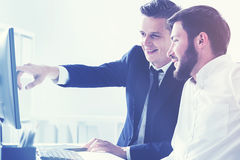 Two business partners pointing at a computer screen Royalty Free Stock Photo