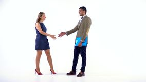 Two business partners shake hands welcoming each other in studio. Businesswoman and businessman shake hands welcoming each other in studio stock footage