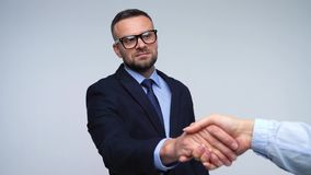 Two business partners shake hands welcoming each other in studio. Slow motion. Businesswoman and his partner shake hands welcoming each other in studio. Slow stock footage