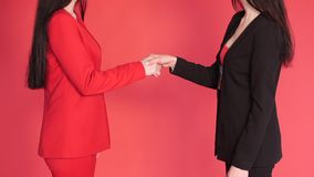 Two business partners shaking hands in agreement on red background. Studio close up of unrecognizable successful businesswomen in red and black suits shaking stock video footage