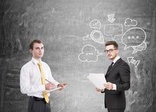 Two business partners, speech bubbles, chalkboard Stock Photo