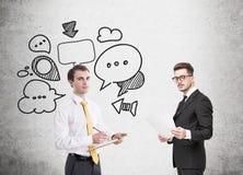 Two business partners, speech bubbles, concrete Stock Photos