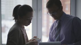 Two business partners standing by the window in office and interacting. silhouettes. Two business partners standing by the window in office and interacting stock footage
