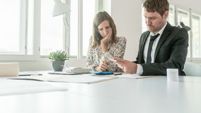 Two business partners summing up the numbers on a printout receipt. While making financial report as they sit together at an office table stock photos