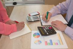 Two business people accountants counting on calculator income for tax form completion hands royalty free stock image