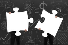 Two business people assembling blank white jigsaw puzzles with d. Two business people assembling blank white jigsaw puzzles on business concept doodles royalty free illustration