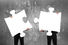 Two business people assembling white jigsaw puzzles with concrete wall royalty free stock photo