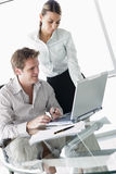 Two business people in boardroom with laptop Royalty Free Stock Image