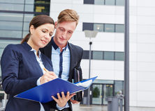 Two business people checking files Stock Photography