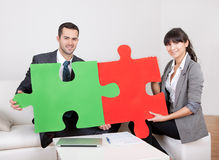 Two business people connecting puzzle pieces. At the office. Teamwork concept Royalty Free Stock Photography