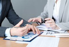 Two business people discuss economic issues. Sitting at the business table with documents Royalty Free Stock Images