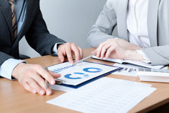 Two business people discuss meeting targets. Sitting at the business table with documents Stock Photo