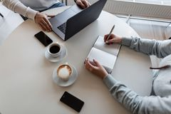 Two business people discuss working moments and drink coffee while sitting at a table in a cafe. Freelancer man remotely working. Two business people discuss stock image