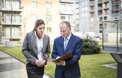 Two business people discussing outside the office Stock Photography