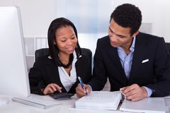Two business people doing finance work Royalty Free Stock Image
