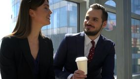 Two business people drink coffee. Two business people talking and drinking coffee at break in office stock footage