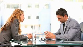 Two business people in gray suit having a meeting. At a desk stock video footage
