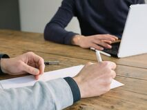 Free Two Business People Have Meeting Round A Wooden Table At An Office. One Writing One Typing On Laptop Royalty Free Stock Photos - 185897298