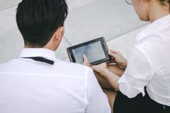 Two business people holding digital tablet and pointing on blank screen with serious expression stock photography