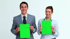 Two business people holding signs. In a studio stock video footage