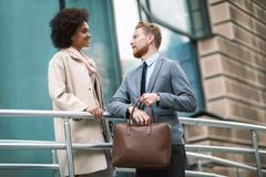 Two business people in an informal conversation. In front of a business building royalty free stock photos